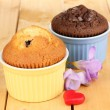 Cupcakes in bowls for baking on wooden table — Stock Photo