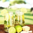 Glasses of cocktail with lime and mint on wooden table on bright background — Стоковая фотография