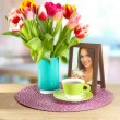 Beautiful tulips in bucket with cup of tea on table in room - Стоковая фотография