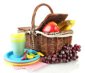 Picnic basket with fruits and tableware isolated on white — Stock Photo