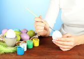 Young woman painting Easter eggs, on color background — Stock Photo