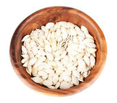 Pumpkin seeds in wooden bowl isolated on the white — Stock Photo