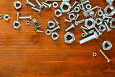 Bolts, screws and nuts on wooden table — Stock Photo