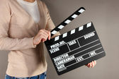 Movie production clapper board in hands on grey background — Stok fotoğraf