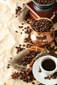 Cup of coffee, pot and grinder on beige background — Stock Photo