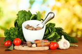 Composition of mortar, spices, tomatoes and green herbs, on bright background — Stock Photo