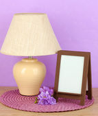 Brown photo frame and lamp on wooden table on lilac wall background — Stockfoto