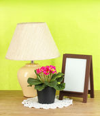 Brown photo frame and lamp on wooden table on green wall background — Stockfoto