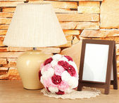 Brown photo frame and lamp on wooden table on stone wall background — Stock fotografie
