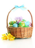 Bright easter eggs with bows in basket, isolated on white — Stock Photo