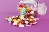 Assortment of pills, tablets and capsules on purple background — Stock Photo