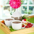 Cups of tea with flower and cake on wooden tray on table in room — Stock Photo #21644141