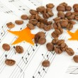 Decorative stars from dry orange peel with coffee beans on musical notes — Stock Photo