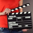 Movie production clapper board in hands on grey background — Stockfoto