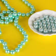 Stock Photo: Beads on yellow background