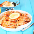 Shrimps with lemon on plate on wooden table close-up — Stock Photo
