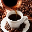 Cup and pot of coffee on coffee beans background — Stock Photo #21644757