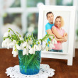 Bouquet of snowdrop flowers in glass vase, on wooden table, bright background — Stock Photo