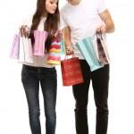 Ungt par shopping och hålla många påsar isolerad på vit — Stockfoto