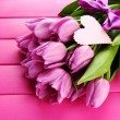 Beautiful bouquet of purple tulips on pink wooden background — Stock Photo #21649699