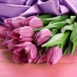Beautiful bouquet of purple tulips on pink wooden background — Stock Photo #21649707