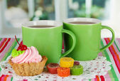 Cups of tea with cake and candy on table in room — Stock Photo