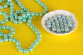 Beads on yellow background — Stock Photo