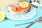 Piece of red fish on plate with with spices and sauce on wooden table close-up — Stock Photo