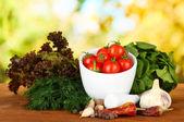 明るい背景に、モルタル、スパイス、トマト、グリーンのハーブの組成 — ストック写真