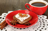Biscuit au chocolat en forme de coeur avec une tasse de café sur le close-up de table en bois — Photo