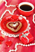 Chocolate cookie in form of heart with cup of coffee on pink tablecloth close-up — Stock Photo