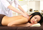 Beautiful young woman in spa salon getting massage, on bright background — Stock Photo