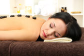 Beautiful young woman in spa salon with spa stones, on bright background — Stock Photo