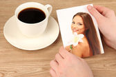 Photo in hands and cup of coffee on wooden table — Stock Photo