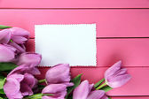 Beautiful bouquet of purple tulips and blank card on pink wooden background — Stock fotografie