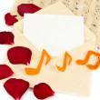 Old envelope with blank paper and dried rose petals on music sheets close up — Stock Photo #21768381