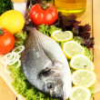 Royalty-Free Stock Photo: Fresh dorado on chopping board with lemon and vegetables on wooden table