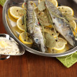 Fish in frying pan with spices and lemon on wooden table close-up — Stock Photo