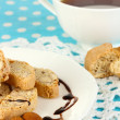 Aromatic cookies cantuccini on plate with cup of coffee on blue tablecloth close-up - Stock Photo
