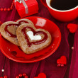 Chocolate cookies in form of heart with cup of coffee on pink tablecloth close-up — Stock Photo #21769535