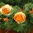 Christmas wreath decorated with rose from dry orange peel on wooden table — Stock Photo