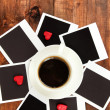 Cup of coffee on worktable covered with photo frames close up — Stock Photo #21769893