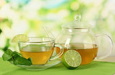 Cup of tea with mint and lime on table on bright background — Стоковое фото