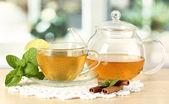 Xícara de chá com hortelã, limão e canela na mesa na sala — Foto Stock