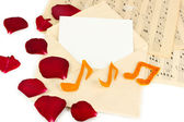 Old envelope with blank paper and dried rose petals on music sheets close up — Foto de Stock