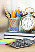 School supplies with clock on wooden table — Stock Photo