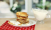 Sweet pancakes on plate with sour cream on table in kitchen — Stock Photo