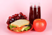 Sandwich on plate with fruit and juice on pink background — Stock Photo
