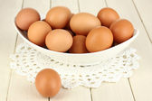 Eggs in white bowl on wooden table close-up — Stock Photo