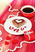 Biscuit au chocolat en forme de coeur avec une tasse de café le gros plan nappe rose — Photo